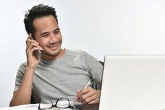 Homme de jeune entreprise souriant tout en parlant au téléphone et ayant l'amusement au travail Photo libre de droits