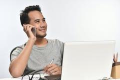 Homme de jeune entreprise souriant tout en parlant au téléphone et ayant l'amusement au travail Photo stock