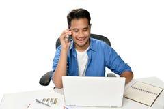 Homme de jeune entreprise souriant tout en parlant au téléphone et ayant l'amusement au travail Photographie stock