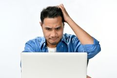 Homme de jeune entreprise tenant sa tête semblant soumise à une contrainte tout en travaillant sur un ordinateur portable Photos libres de droits