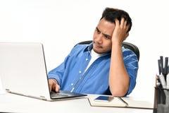 Homme de jeune entreprise tenant sa tête semblant soumise à une contrainte tout en travaillant sur un ordinateur portable Image libre de droits
