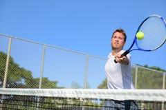 Homme de joueur de tennis frappant la boule dans une volée Photo stock