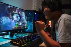 Homme de l'adolescence asiatique joyeux de gamer jouant des jeux vidéo sur l'ordinateur dans d photographie stock
