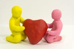 Homme de la pâte à modeler deux tenant le coeur rouge Image stock