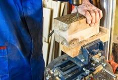 Homme de lieu de travail de charpentier à l'aide d'une foreuse à colonne sur le bois Images libres de droits