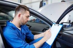 Homme de mécanicien automobile avec le presse-papiers à l'atelier de voiture Photos stock