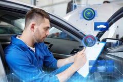 Homme de mécanicien automobile avec le presse-papiers à l'atelier de voiture Images libres de droits