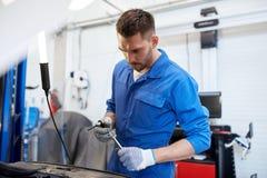 Homme de mécanicien avec la clé réparant la voiture à l'atelier Photo stock