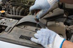 Homme de mécanicien avec la clé réparant la voiture à l'atelier Photo libre de droits