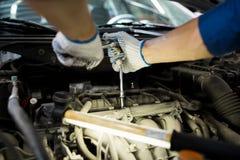 Homme de mécanicien avec la clé réparant la voiture à l'atelier Photographie stock