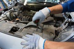 Homme de mécanicien avec la clé réparant la voiture à l'atelier Image stock