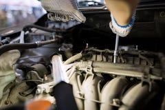 Homme de mécanicien avec la clé réparant la voiture à l'atelier Photos stock