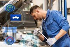 Homme de mécanicien avec la clé réparant la voiture à l'atelier Photos libres de droits
