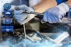 Homme de mécanicien avec la clé réparant la voiture à l'atelier Images libres de droits