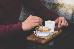 Homme de main de l'Asie de plan rapproché dans la chemise rouge remuant le sucre dans la petite tasse blanche de café chaud photos stock