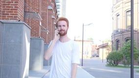 Homme de marche parlant au téléphone avec le fond de bâtiment de grenier, Front View banque de vidéos