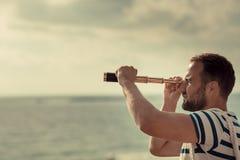Homme de marin regardant par les jumelles Photo stock