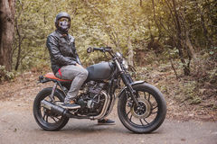 Homme de motard s'asseyant sur sa moto photo stock