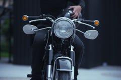 Homme de motard s'asseyant sur sa moto, effet de vintage photographie stock