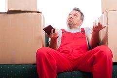 Homme de moteur s'asseyant sur le téléphone et faire des gestes de participation de divan Photographie stock libre de droits