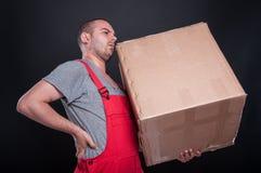 Homme de moteur tenant la boîte ayant des douleurs de dos Photos libres de droits