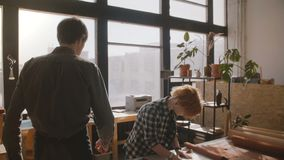 Homme de mouvement lent entrant dans l'atelier de fabrication, artisan féminin coupant le cuir sur une table pour les marchandise banque de vidéos