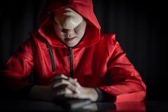 Homme de mystère dans le hoodie rouge se reposant dans l'obscurité images stock