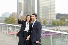 Homme de négociant et femme de directeur d'heure à l'aide du smartphone prenant le sel Photos stock