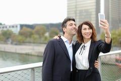 Homme de négociant et femme de directeur d'heure à l'aide du smartphone prenant le sel Image libre de droits