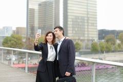 Homme de négociant et femme de directeur d'heure à l'aide du smartphone prenant le sel Photographie stock libre de droits
