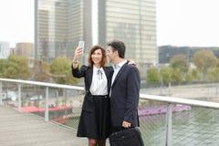 Homme de négociant et femme de directeur d'heure à l'aide du smartphone prenant le sel Photographie stock