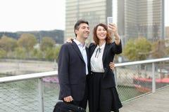 Homme de négociant et femme de directeur d'heure à l'aide du smartphone prenant le sel Photo libre de droits