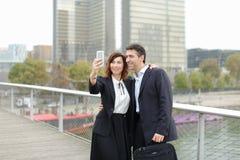 Homme de négociant et femme de directeur d'heure à l'aide du smartphone prenant le sel Photos libres de droits