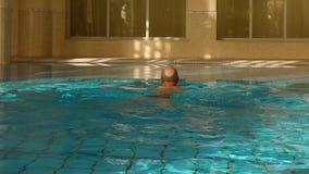 Homme de natation de brasse dans la piscine d'intérieur, vue arrière, mouvement lent banque de vidéos