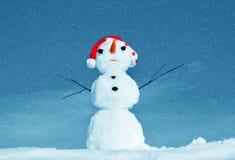 Homme de neige dans le capuchon de Santa sur la nature Photographie stock libre de droits