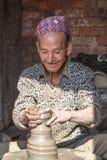 Homme de Nepali appréciant son travail de poterie Photos stock