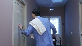 Homme de personnel de nettoyage d'hôtel frappant sur la porte de pièce pour le service de ménage banque de vidéos