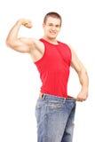 Homme de perte de poids dans une vieille paire de jeans montrant son muscule photographie stock