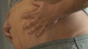 Homme de poids excessif drôle touchant sa graisse de bière devant le miroir, poids supplémentaire banque de vidéos