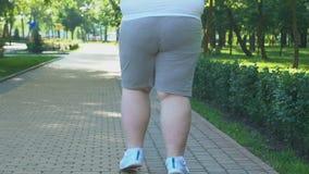 Homme de poids excessif pulsant lentement le long du parc de ville, essayant de perdre le poids, suivant un régime banque de vidéos