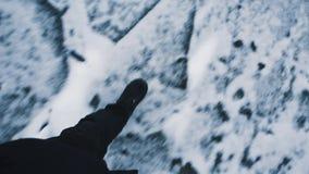 Homme de point de vue dans des vêtements noirs marchant sur la surface gelée de lac clips vidéos