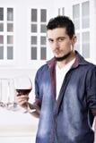 Homme de regard bon heureux rêveur buvant du vin rouge dans la cuisine photo stock