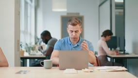 Homme de renversement regardant l'ordinateur portable sur le lieu de travail Nouvelles choquées de lecture d'homme banque de vidéos