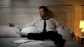 Homme de renversement s'asseyant sur le lit avec des documents autour, désir de s'échapper de l'effort photographie stock