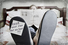 Homme de repos se situant dans le lit et lisant le journal - concept d'amusement Image stock