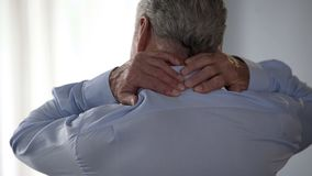 Homme de retraité frottant de retour de son cou, se tenant vers l'arrière, travailleur de bureau photographie stock libre de droits