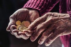Homme de retraité se tenant dans des pièces de monnaie d'euro de mains Thème de basses pensions Images stock