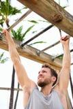 Homme de séance d'entraînement établissant des bras sur l'échelle de brachiation Photos stock