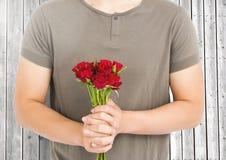 Homme de section médiane tenant le groupe de roses rouges Image stock