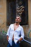 Homme de Sexi dans une chemise blanche et une fenêtre ornementale sur le fond Et receveur rêveur Photographie stock